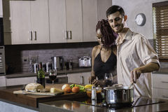 Happy young mixed race couple cooking dinner preparing food in the kitchen Royalty Free Stock Photos
