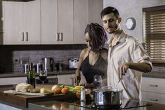 Happy young mixed race couple cooking dinner preparing food in the kitchen Stock Photo