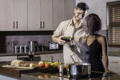 Happy young mixed race couple drinking wine cooking dinner in kitchen Royalty Free Stock Image