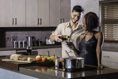Happy young mixed race couple drinking wine cooking dinner in kitchen Stock Photos
