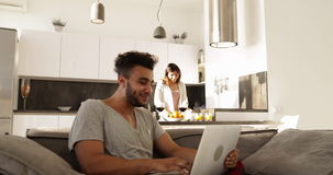 Happy Young Mixed Race Couple Home Interior, Hispanic Man Using Laptop Computer, Asian Woman Cooking Breakfast stock footage