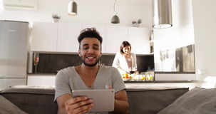 Happy Young Mixed Race Couple Home Interior, Hispanic Man Using Tablet Computer Video Chat, Asian Woman Cooking stock footage