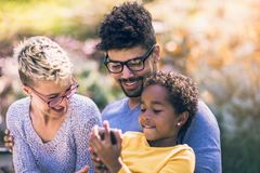 Happy young mixed race couple spending time with their daughter. Using smart phone in public park royalty free stock photo