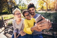 Young mixed race couple spending time with their daughter using smart phone in public park stock images