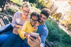 Happy young mixed race couple spending time with their daughter. Using smart phone in public park stock photo