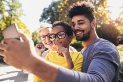Happy young mixed race couple spending time with their daughter using smart phone. In public park royalty free stock photography