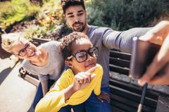 Happy young mixed race couple spending time with their daughter using smart phone. In public park royalty free stock image