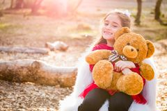 Happy Young Mixed Race Girl Hugging Teddy Bear Outdoors. Cute Young Mixed Race Girl Hugging Teddy Bear Outdoors royalty free stock image
