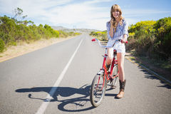 Happy young model posing while riding bike Royalty Free Stock Image