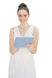 Happy young model in white dress holding tablet computer Stock Photo