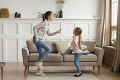 Happy mom and little kid daughter laughing dancing at home royalty free stock images