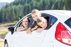 Happy young mom and her children sitting in a car. Happy young women and her children sitting in a car and look out from windows. Family travel background image Stock Photos