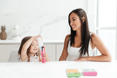 Happy young mom with little daughter drawing with pencils. Royalty Free Stock Images