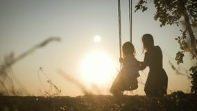 Happy young mom with a little girl swinging in the park together at sunset. Mother and daughter riding on swing, family stock video footage
