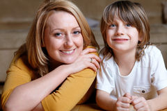 Happy young mom lying on floor with her son Royalty Free Stock Photos