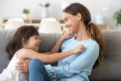 Playful mom and daughter relax having fun at home. Happy young mom and preschooler funny daughter relax on couch at home having fun together, playful mother stock photos