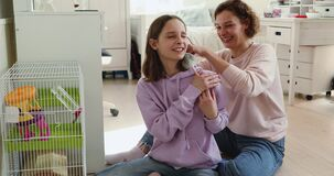 Happy mom and teenage daughter playing with rat at home
