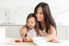 Free Happy Young Mom With Little Cute Asian Daughter Cut Strawberry Stock Photos - 98581243