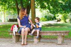 Happy young mother and adorable toddler girl walking through sum Stock Photography
