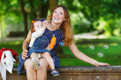 Happy young mother and adorable toddler girl walking through sum Stock Photos