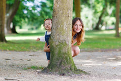 Happy young mother and adorable toddler girl walking through sum Stock Image