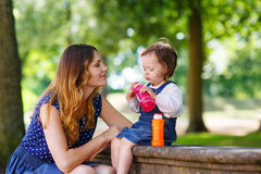 Happy young mother and adorable toddler girl walking through sum Stock Images