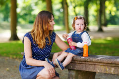 Happy young mother and adorable toddler girl walking through sum Royalty Free Stock Images