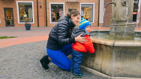 Happy young mother with baby boy looking at fountain on street stock footage