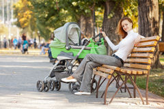 Happy young mother with baby in buggy. Sitting on bench in autumn park Stock Images