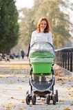 Happy young mother with baby in buggy. Walking in autumn park Royalty Free Stock Image