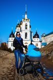 Happy young mother with baby in buggy Stock Photos