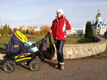 Happy young mother with baby in buggy. Walking in autumn park Stock Image