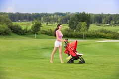 Happy young mother with baby in buggy walking. A young mother posing with a baby stroller in a park Royalty Free Stock Photos