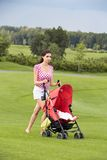 Happy young mother with baby in buggy walking. A young mother posing with a baby stroller in a park Stock Photos