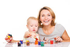Happy young mother with a baby paint by hands. Royalty Free Stock Image