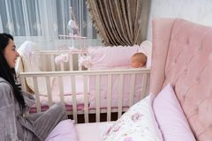 Happy young mother and baby in pink bedroom scene. stock photography