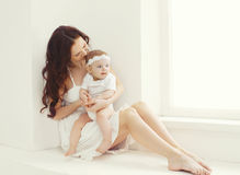 Happy young mother and baby together at home in white room Royalty Free Stock Photos