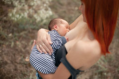 Happy young mother breastfeed newborn baby on walk. Royalty Free Stock Photography