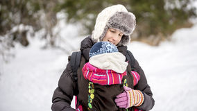 Happy young mother carrying her baby in a carrier Royalty Free Stock Photos
