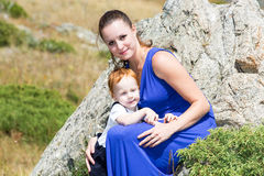 Happy young mother with child boy on nature. The concept cheerful childhood family royalty free stock images
