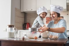 Happy young mother and child in chef hats preparing dough. At kitchen stock photos