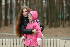 Happy young mother and child daughter hugging posing on bench in spring park. Outdoors Stock Photography