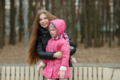 Happy young mother and child daughter hugging posing on bench in spring park. Outdoors Royalty Free Stock Photography