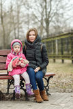 Happy young mother and child daughter hugging sitting on bench in spring park. Outdoors Stock Images