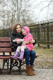 Happy young mother and child daughter hugging sitting on bench in spring park Stock Images