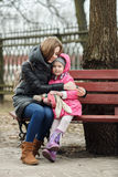 Happy young mother and child daughter hugging sitting on bench in spring park. Outdoors Royalty Free Stock Image