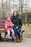 Happy young mother and child daughter hugging sitting on bench in spring park. Outdoors Stock Photo