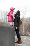 Happy young mother and child daughter kissing on strolling spring city park. Outdoors Stock Photo