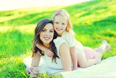 Happy young mother and child daughter together on grass in summer Stock Photos