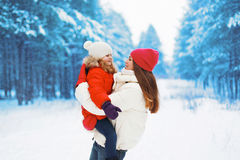 Happy young mother and child having fun outdoors in winter Stock Photos
